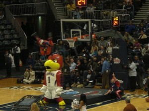 Atlanta Hawks mascot jumping on a trampoline, over the Zooperstar like Hawk blowup and dunking the ball into the net...He missed....twice...